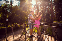 Romantic young couple kissing  and stand to bridge on background summer forest. Romantic young couple kissing  and stand to  bridge on background summer forest Royalty Free Stock Image