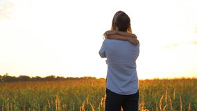 Romantic young couple is kissing on a sunset with sun shining bright behind. Them on a horizon stock video footage
