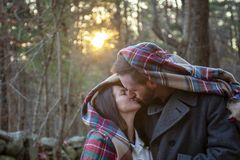 Romantic young couple kissing under a blanket in the New England woods stock photo