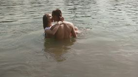 Romantic young couple in lake kissing while embracing. Handsome young man holding his pretty girlfdriend on hands stock video