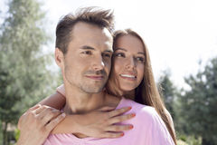 Romantic young couple looking away in park Royalty Free Stock Photography