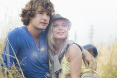 Romantic young couple looking away while sitting in field Stock Images