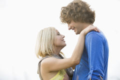 Romantic young couple looking at each other against clear sky Stock Photos
