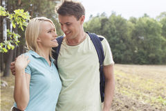 Romantic young couple looking at each other while hiking in forest Stock Images