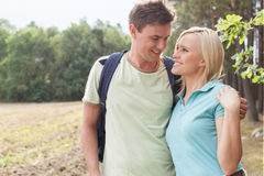 Romantic young couple looking at each other while hiking in forest Stock Photo