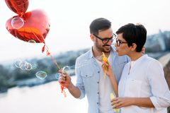 Romantic young couple dating outdoor and blowing bubbles. Romantic young couple in love dating outdoor and blowing bubbles Stock Photo