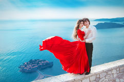 Romantic young couple in love. Fashion girl model in blowing red Royalty Free Stock Photo
