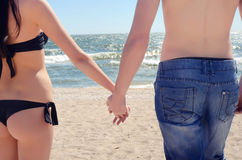 Romantic young couple in love holding hands on the beach. Sexy girlfriend and boyfriend holding hands at the seaside. Stock Photography