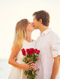 Romantic Young Couple in Love, Man holding surprise bouquet of r Royalty Free Stock Photography
