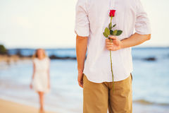 Romantic Young Couple in Love, Man holding surprise rose for beautiful young woman stock photography