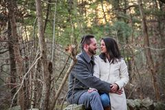 Romantic young couple in the New England woods. A romantic young couple sitting on a rock wall in the New England woods on a cold fall day with sun setting royalty free stock photo