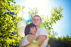 Romantic young couple outdoors with helium balloons Royalty Free Stock Photos