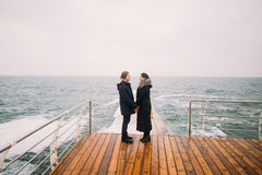 Romantic young couple on a pier looking away, back view, seascape background Royalty Free Stock Images