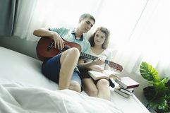 Romantic young couple playing the guitar in bed together royalty free stock image
