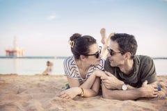Romantic couple relaxing on a beach Stock Photos