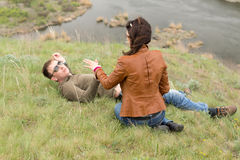 Romantic young couple relaxing near a river Stock Photos