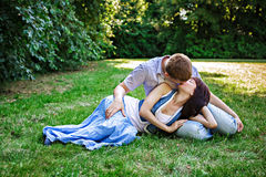 Romantic young couple relaxing in park and kissing Stock Photography