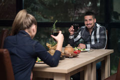 Romantic Young Couple At Restaurant Table Toasting Stock Images