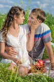 Romantic young couple resting outdoors and tenderlt touching eac Royalty Free Stock Photography