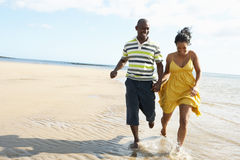 Romantic Young Couple Running Along Shoreline. Of Beach Holding Hands Royalty Free Stock Image
