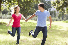 Romantic Young Couple Running Through Countryside Stock Photo