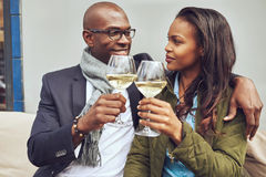 Romantic young couple share a toast. Romantic young African American couple share a toast clinking their glasses of white wine as the look deeply into each royalty free stock image