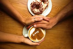 Romantic Young Couple Sit In Cafe,closeup Hands Holding A Cup Of Coffee With Heart On It And 2 Donuts On Wooden Table Background Stock Image