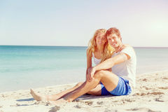 Romantic young couple sitting on the beach Royalty Free Stock Image