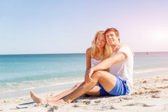 Romantic young couple sitting on the beach Stock Image