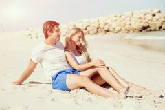 Romantic young couple sitting on the beach Royalty Free Stock Photography