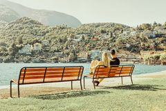 Romantic young couple sitting in bench in Ascona luxury resort. Romantic young couple sitting in bench in Ascona luxury tourist resort on Lake Maggiore in Ticino royalty free stock photography