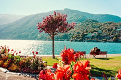 Romantic young couple sitting on bench in Ascona luxury resort. Romantic young couple sitting on bench in Ascona luxury tourist resort on Lake Maggiore in Ticino royalty free stock photo