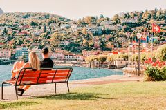 Romantic young couple sitting on bench at Ascona luxury resort. Romantic young couple sitting on bench at Ascona luxury tourist resort on Lake Maggiore in Ticino royalty free stock images