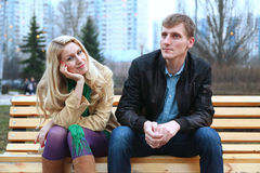 Romantic young couple sitting on a bench. At evening stock photo