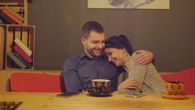 Romantic young couple sitting in a cafe at a table drinking coffee and talking. Dolly stock video footage