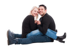 Romantic young couple sitting on floor andsmiling stock photography