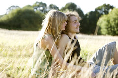 A romantic young couple sitting on the grass in summertime Royalty Free Stock Photos