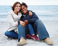 Romantic young couple sitting together on beach Royalty Free Stock Photos