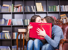 Romantic young couple sneaking a kiss Stock Photography