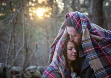 Romantic young couple snuggle under a blanket in the New England woods. A romantic young couple snuggling under a plaid blanket in the New England woods on a royalty free stock photo