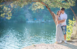 Romantic young couple standing on cliff over river Stock Photography