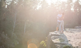 Romantic young couple standing on cliff over river before sunset Royalty Free Stock Photography