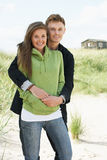 Romantic Young Couple Standing By Dunes Stock Photo