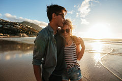 Romantic young couple standing together on beach. Outdoor shot of romantic young couple standing together on beach. Young men and women on seashore at sunset Stock Photography
