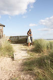 Romantic Young Couple Standing By Wooden Fence. Of Beach Hut Amongst Dunes Stock Images