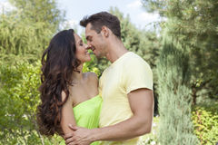 Romantic young couple about to kiss in park Royalty Free Stock Photography