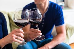 Romantic young couple toasting with red wine while sitting on th Stock Photo