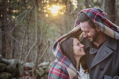 Romantic young couple under a blanket in the forest. A romantic young couple under a blanket in the woods on a cold fall day with sun setting behind them royalty free stock photography