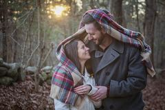 Romantic young couple under a blanket in the forest. A romantic young couple under a blanket in the woods on a cold fall day with sun setting behind them stock photography