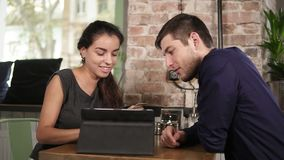 Romantic young couple using tablet and paying with the credit card sitting at the tablet in coffee shop. Smart, fast and stock video footage